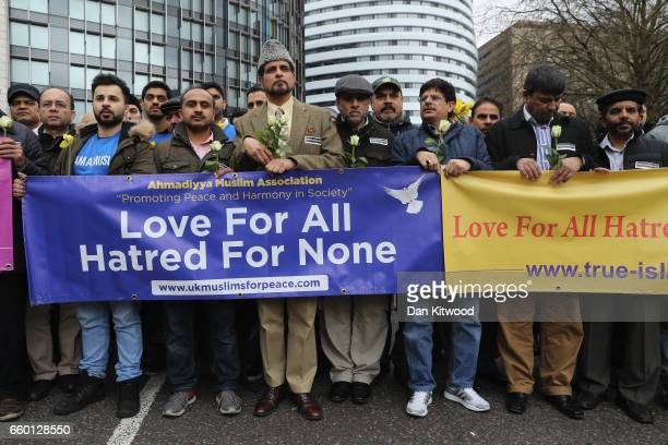 People hold a banner reading 'Love for all hatred for none' on Westminster Bridge as they attend a vigil to remember the victims of last week's...