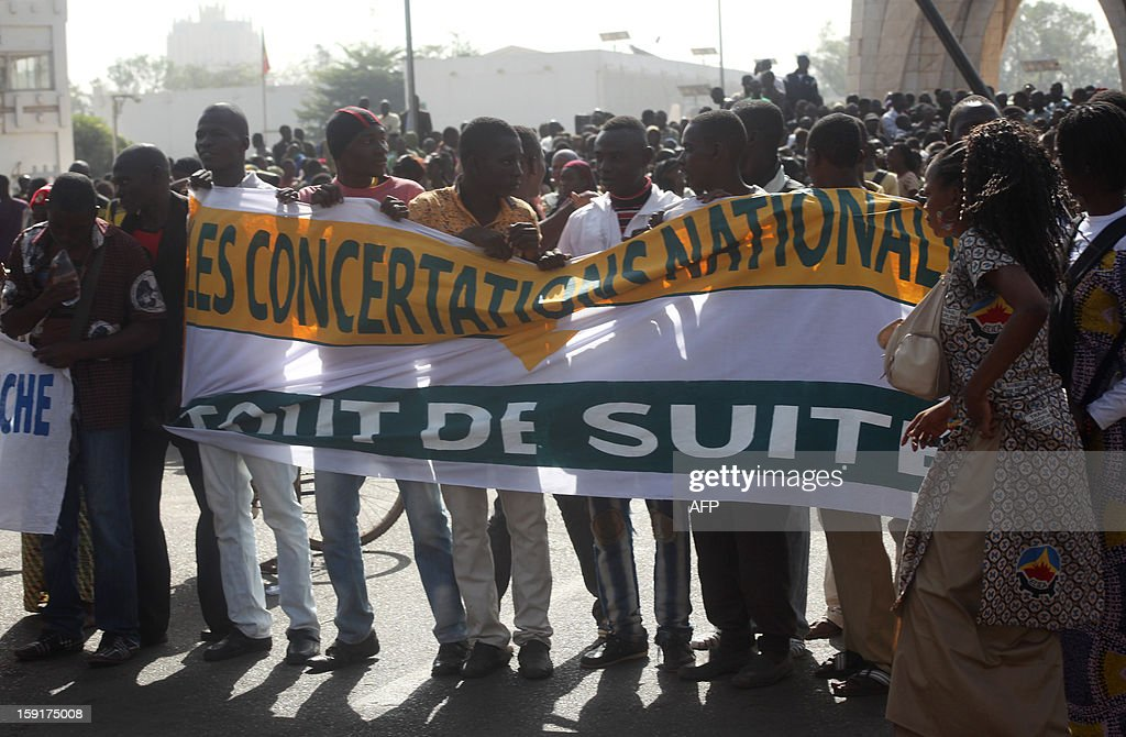 People hold a banner reading '' national concertations, right now'' during a demonstration on January 9, 2013 in Bamako to ask for ''immediate days of sovereign consultation'' on the transition in Mali. Mali, once considered one of the region's most stable democracies, was plunged into crisis by a March 22 coup that overthrew the elected government and created a power vacuum that enabled Ansar Dine and two Al-Qaeda-linked Islamist groups to seize control of the vast desert north. NATO said on January 9 that it had not been asked to assist a military alliance in resolving the armed conflict in Mali as Burkina Faso's president pushed for renewed talks between Islamist fighters and the Malian government. AFP PHOTO / Habibou Kouyate
