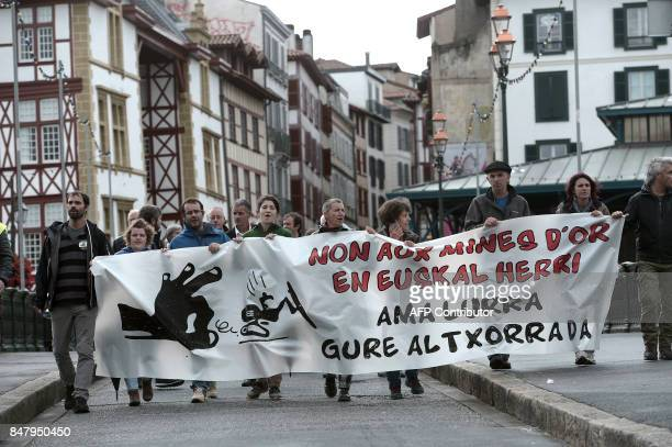 People hold a banner reading 'No to gold mines in Basque country our land is our treasure' as they take part in a demonstration to protest against a...