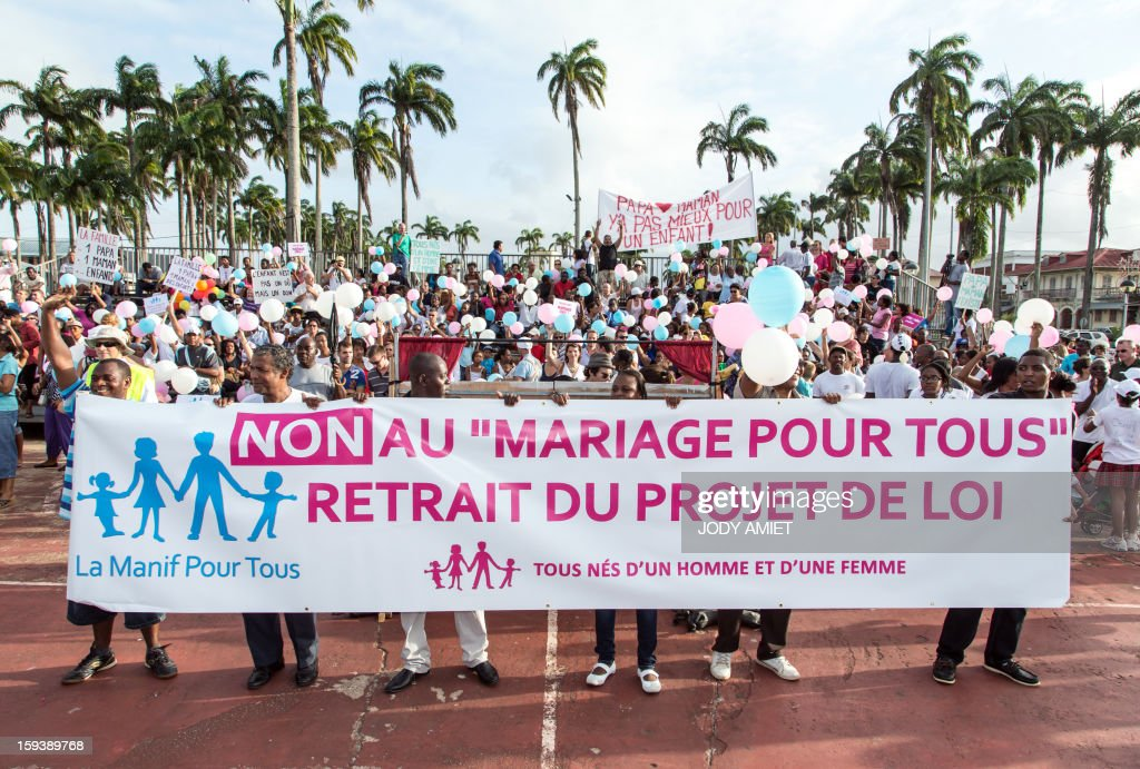 People hold a banner reading ''No to marriage for all, withdrawal of the draft bill, all born of a man and a woman '' during a protest against same-sex marriage, in Cayenne, in French Guiana, on January 12, 2013. Tens of thousands are set to march in Paris, on January 13, 2013 to denounce government plans to legalise same-sex marriage and adoption which have angered many Catholics and Muslims, France's two main faiths. The French parliament is to debate the bill -- one of the key electoral pledges of Socialist President at the end of this month.