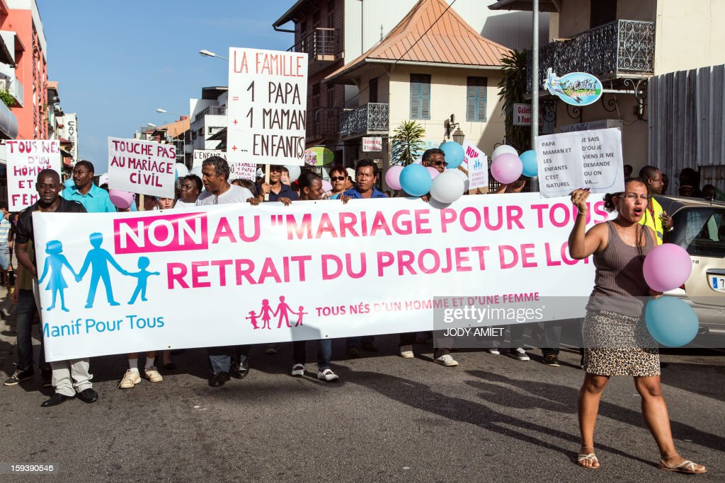 People hold a banner reading ''No to marriage for all, withdrawal of the draft bill, all born of a man and a woman'' during a protest against same-sex marriage, in Cayenne, in French Guiana, on January 12, 2013. Tens of thousands are set to march in Paris, on January 13, 2013 to denounce government plans to legalise same-sex marriage and adoption which have angered many Catholics and Muslims, France's two main faiths. The French parliament is to debate the bill -- one of the key electoral pledges of Socialist President at the end of this month. AFP PHOTO/JODY AMIET