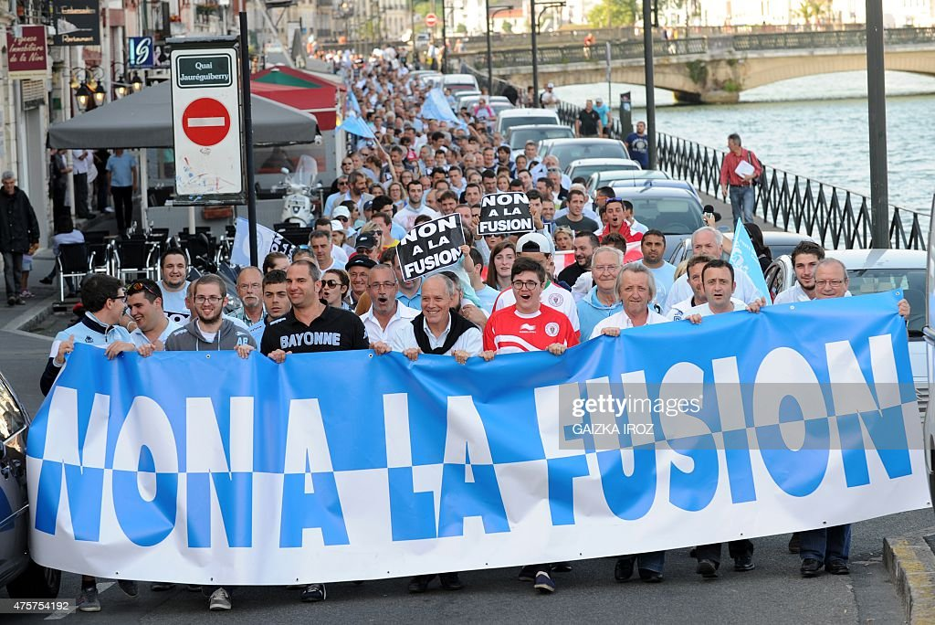 People hold a banner reading 'no to the merger' as they take part in a protest against the possible merger of two French rugby clubs Aviron Bayonnais...