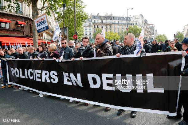 People hold a banner reading 'Police in mourning' during a demonstration of French police officers called by the union UniteSGP Police FO in Paris on...