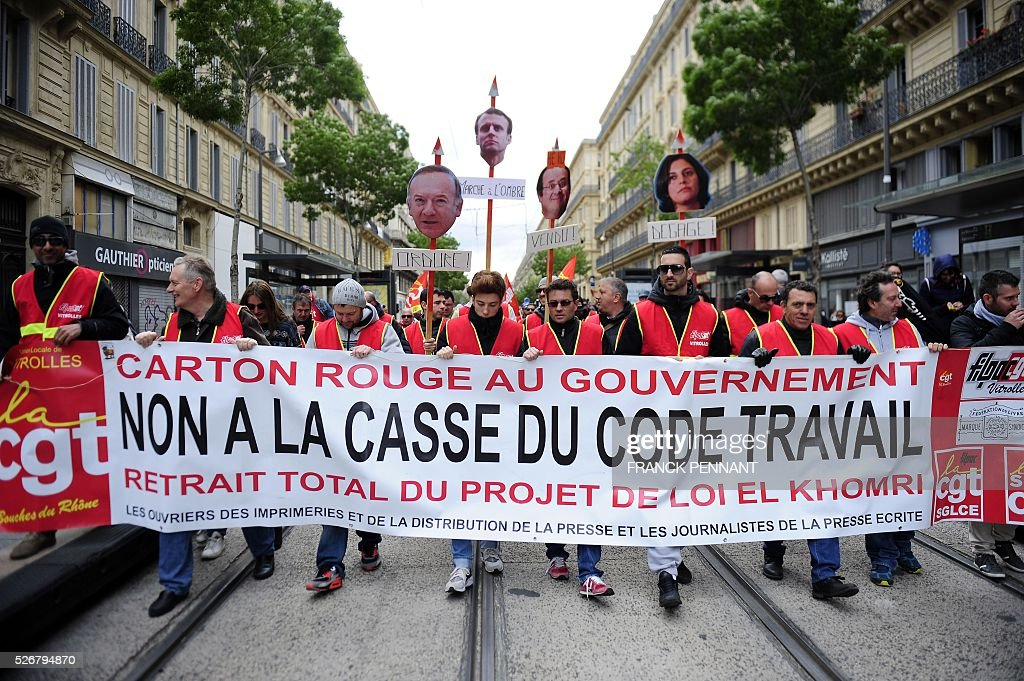 People hold a banner reading 'Red card for the governement, no to the destruction of the labour code, total withdrawal of the labour draft law by El Khomri' as they demonstrate in the streets of Marseille during the traditional May Day rally on May 1, 2016. / AFP / Franck PENNANT