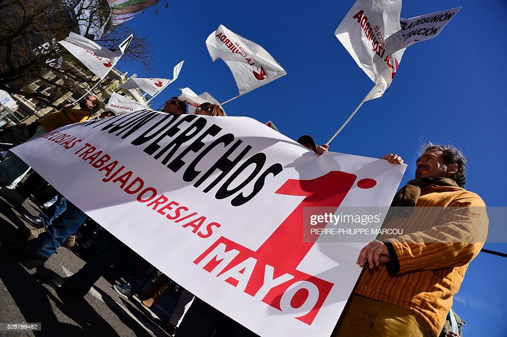 People hold a banner reading 'Rights for workers' during traditional May Day rally in Madrid on May 1, 2016. / AFP / PIERRE