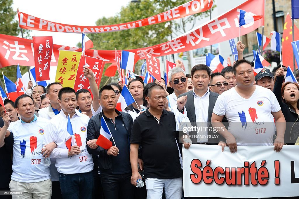 People hold a banner reading 'Security Freedom Equality Brotherhood' during a demonstration in Paris on August 21 organised by several associations...