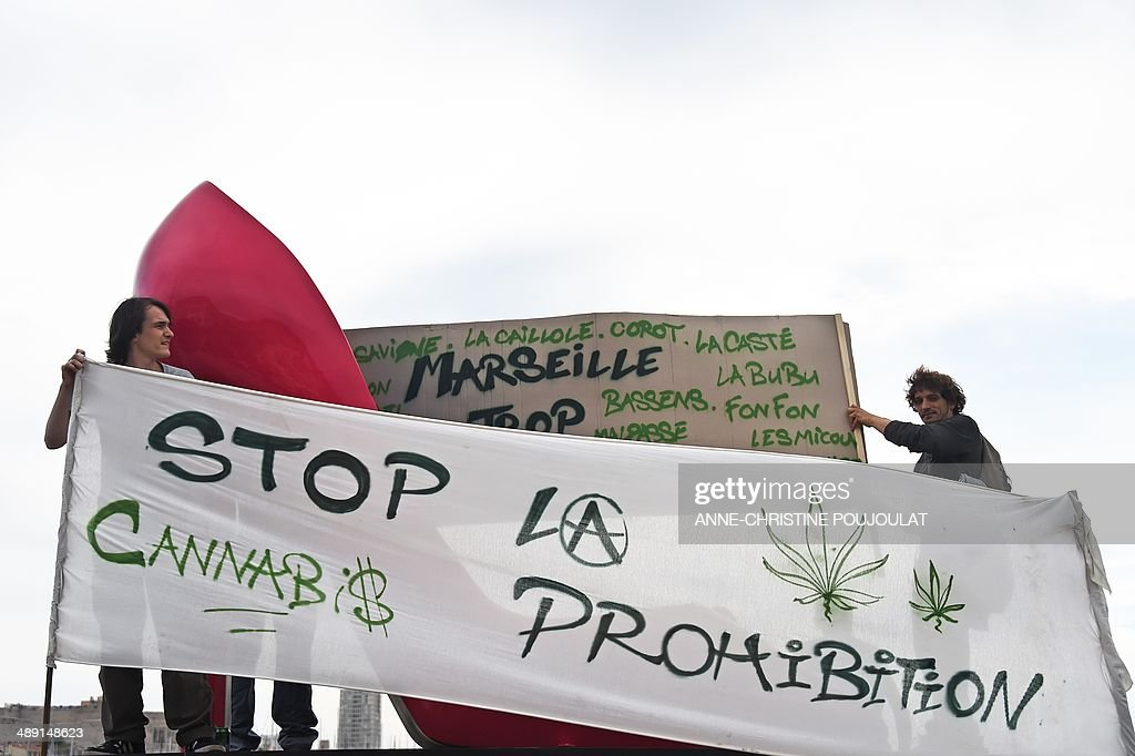 People hold a banner reading 'Stop the prohibition' during a protest to call for the legalization of marijuana on May 10, 2014, at the Old Harbour in Marseille, southern France. About 147 million people globally -- or about 2.5 percent of the population -- use cannabis, according to the World Health Organization. AFP PHOTO / ANNE-CHRISTINE POUJOULAT