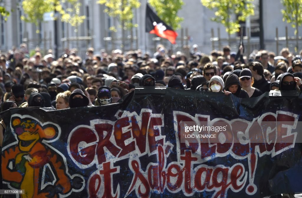 People hold a banner reading 'Strike, blockade and sabotage' as they march during a protest against the government's planned labour law reforms in Nantes, western France, on May 3, 2016. High school pupils and workers protested against deeply unpopular labour reforms that have divided the Socialist government and raised hackles in a country accustomed to iron-clad job security. / AFP / LOIC