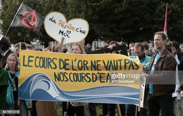 People hold a banner reading 'The price of gold does not worth our rivers' as they take part in a demonstration to protest against a project of the...