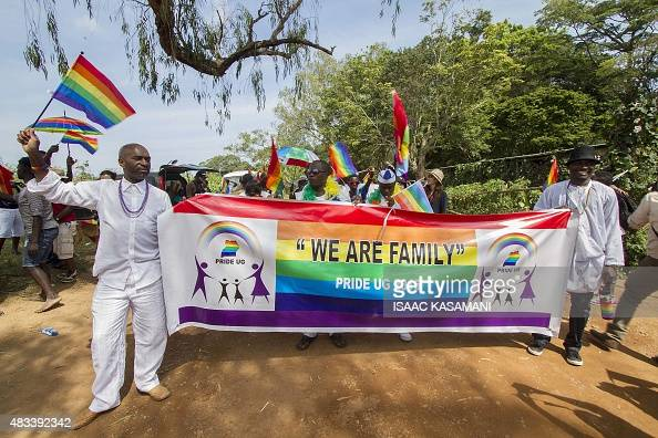 People hold a banner reading 'We are Family' while waving rainbow flags as they take part in the Gay Pride parade in Entebbe on August 8 2015 Ugandan...