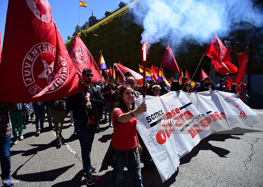 People hold a banner reading 'We are the working class' during traditional May Day rally in Madrid on May 1, 2016. / AFP / PIERRE