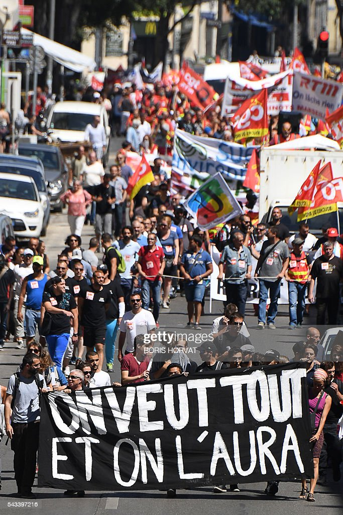 People hold a banner reading 'We want it all and we will' and flags as they take part in a demonstration against the French government's planned labour law reforms, on June 28, 2016 in Marseille, southern France. Unions have called repeated strikes and marches in opposition to the law, which seeks to bring down France's intractable 10-percent unemployment rate by making it easier to hire and fire workers. / AFP / BORIS