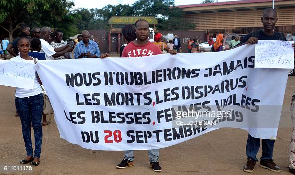 People hold a banner reading 'We will never forget the dead the missing the wounded and the raped women of September 28 2009' in Conakry on September...