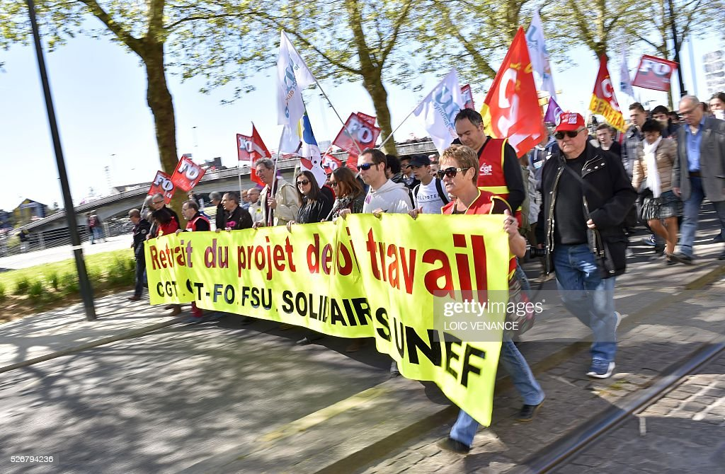 People hold a banner reading 'withdrawal of the labour law reform project' as they take part in the traditional May Day rally in Nantes, western France, on May 1, 2016. / AFP / LOIC
