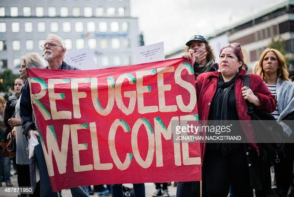 People hold a banner 'refugees welcome' as they take part in a demonstration in solidarity with refugees seeking asylum in Europe after fleeing their...