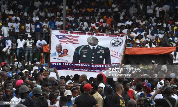People hold a banner supportin former international Liberian football star turned politician George Weah during a presidential campaign rally in...