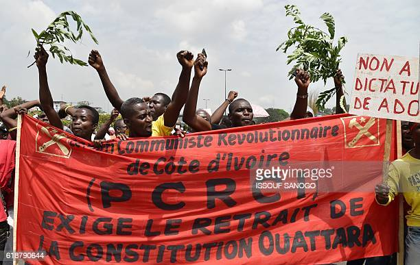 People hold a banner that reads in French 'We demand the withdrawl of the constitution Ouattara' as they gesture and chant slogans during a protest...