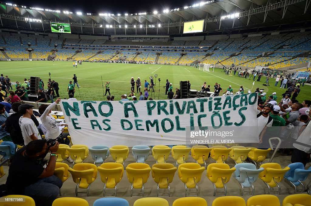 People hold a banner to protest against the Mario Filho --Maracana-- stadium privatization and the demolition of the former Indigenous Museum during a test event, in Rio de Janeiro on April 27, 2013. The Maracana stadium will host the upcomig Confederations Cup --next June--, the Brazil 2014 FIFA World Cup and the 2016 Summer Olympics.
