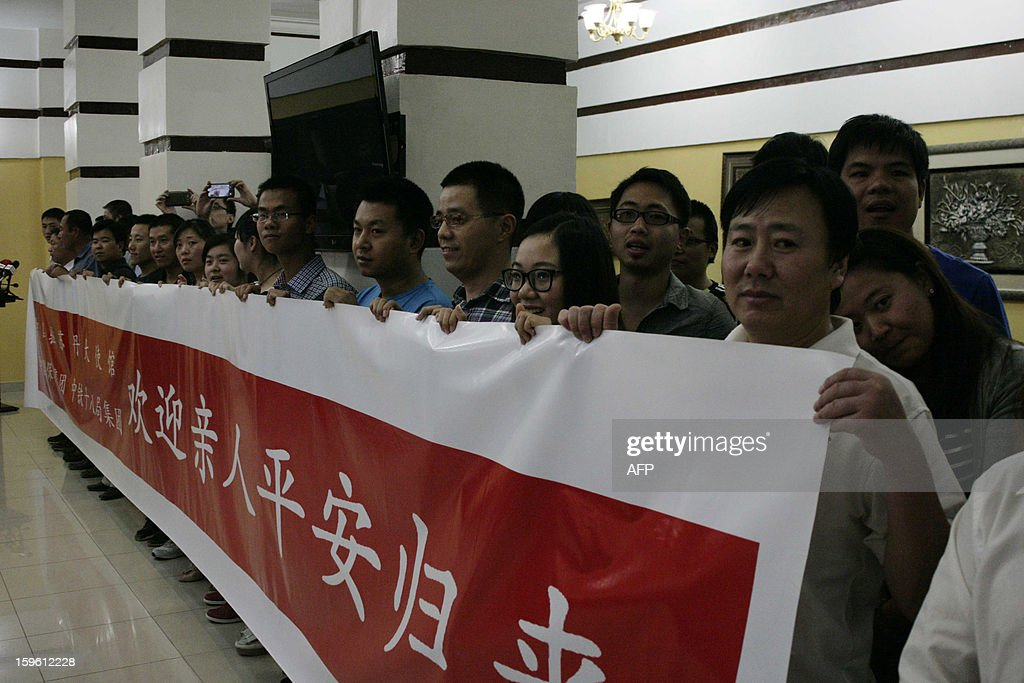 People hold a banner to welcome Chinese workers abducted by Darfur rebels earlier this month, who arrive at the Khartoum airport after their release on January 17, 2013. Four Chinese workers abducted by Darfur rebels on January 12 have been freed, a spokeswoman for the joint UN-African Union peace keeping force in the troubled western Sudan region.