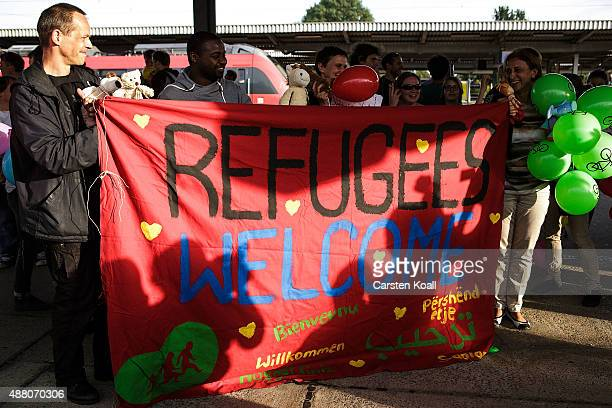 People hold a banner to welcome migrants arriving on an ICE highspeed train of Deutsche Bahn from Munich near Berlin on September 13 2015 in...