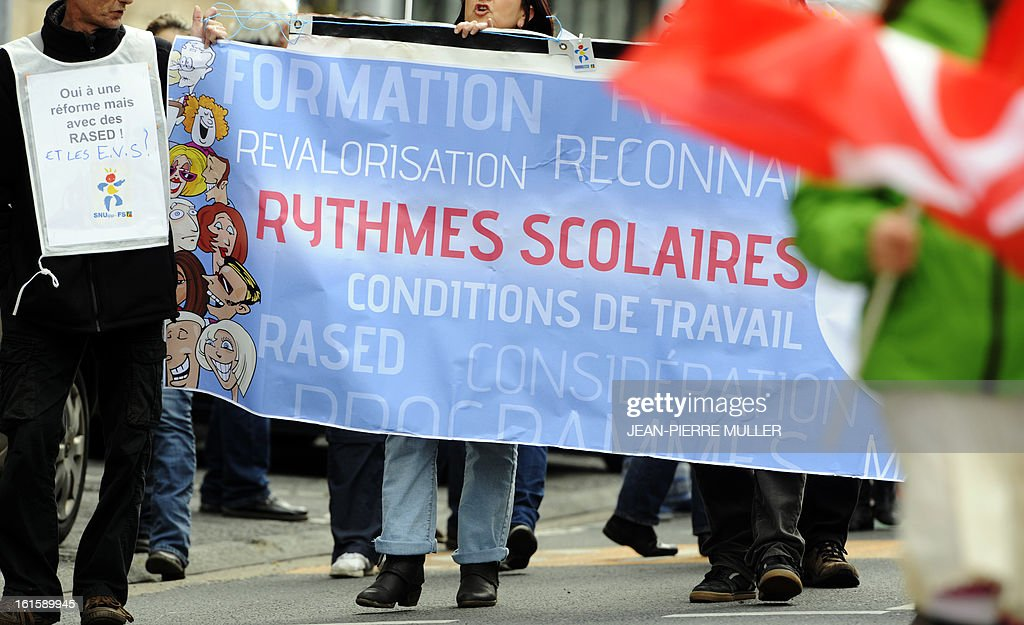 People hold a banner which claim for their working conditions and for the respect of the rhythms of schooling as they demonstrate on February 12, 2013 in Lyon, eastern france, as part of a nationwide strike day over the government's plans to make children attend classes five days a week, instead of the current four. The government recently issued a decree introducing a half day of school on Wednesdays for children 3 to 11 starting in September, while reducing the school day by 45 minutes the rest of the week.