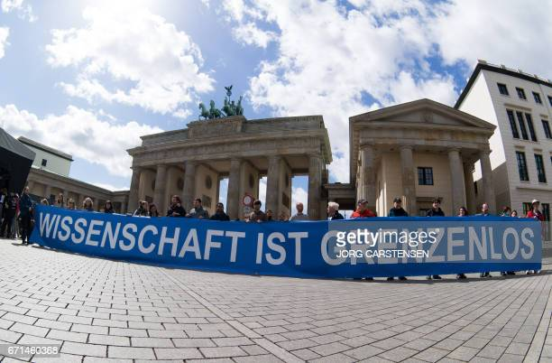 People hold a banner which reads 'Science is borderless' as they take part in the March for Science in front of the Brandenburg Gate in Berlin on...