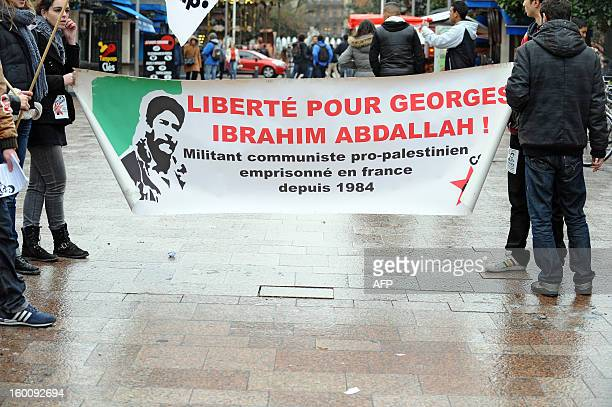 People hold a banner with a portrait of Georges Ibrahim Abdallah a propalestinian militant and reading 'Freedom for Georges Ibrahim Abdallh' during a...