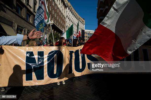 People hold a banner with a sign reading 'No Ius Soli'during a march in downtown Rome on October 14 2017 About two thousand people took to the...