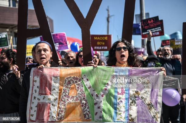 People hold a benner reasing 'No' as they shout slogans while they march over the Galata bridge on April 2 in Istanbul during a protest against the...