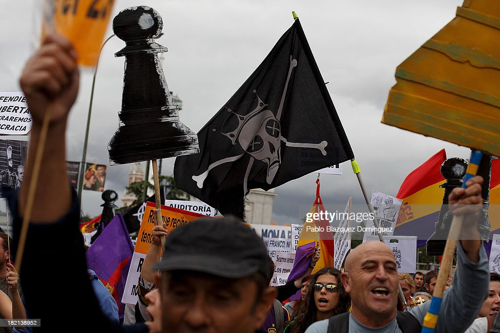 People hold a black flag showing 'a skull and crown' during a demonstration against the Spanish Monarchy under the header 'Check the King' at Princesa Street on September 28, 2013 in Madrid, Spain. Organizers call for a demonstration on the anniversary of 'Surround the congress protest' to claim the abolition of the Monarchy. Currently King Juan Carlos of Spain is in hospital recovering from a hip operation. The Spanish Royal Family has lost popularity since the King injured his hip on elephant hunting trip and the King's son-in-law, Inaki Urdangarin is being investigated over a corruption scandal.