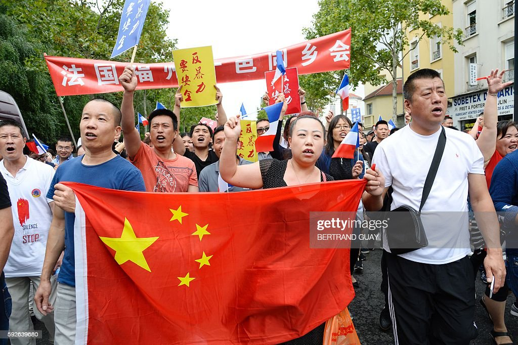 People hold a Chinese national flag as they march during a demonstration in Paris on August 21 organised by several associations of the Chinese...