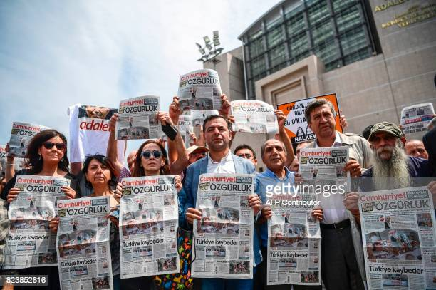 People hold a copy of today's Cumhuriyet daily newspaper on July 28 2017 during a demonstration in front of Istanbul's courthouse A Turkish court was...