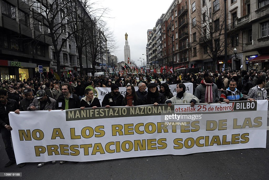 People hold a giant banner reading 'Against cuts in social services' during a demonstration against the government's new labour reform law and cuts in social services on February 25, 2012 in the Northern Spanish Basque city of Bilbao. The conservative government that took power in December 2011 after a landslide election victory has launched a tough programme of reforms and spending cuts and is pressuring the big-spending regions to do their bit.