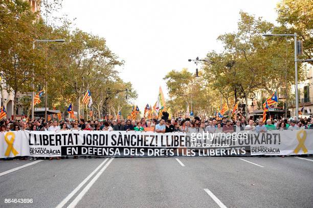 People hold a giant banner reading 'Freedom for Jordi Sanchez Freedom for Jordi Cuixart' during a demonstration on October 21 2017 in Barcelona to...