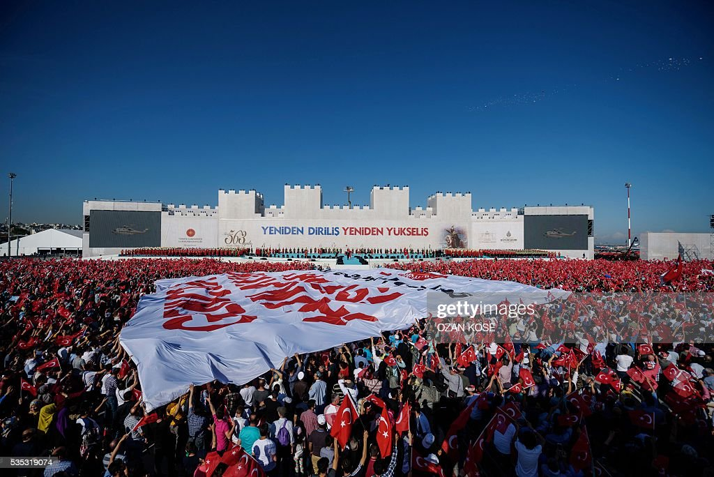 People hold a giant banner reading 'Turkish youth wants Presidency System' during a rally to mark the 563rd anniversary of the conquest of Istanbul by Ottoman Turks on May 29, 2016 in Istanbul. / AFP / OZAN