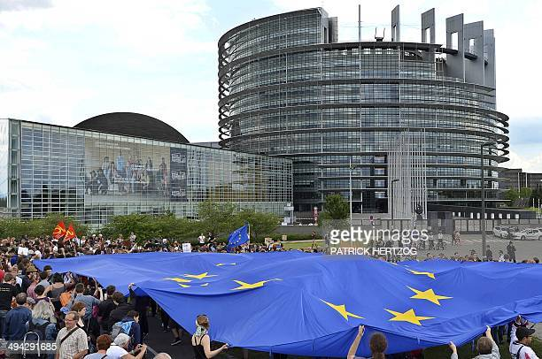 People hold a giant European Union flag as they take part in a demonstration against the French farright party Front National following the vote for...