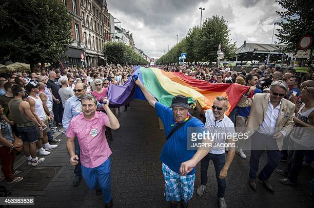 People hold a giant rainbow flag as they take part in the 7th edition of the 'Antwerp Pride' parade organised by lesbian gay bisexual and transgender...
