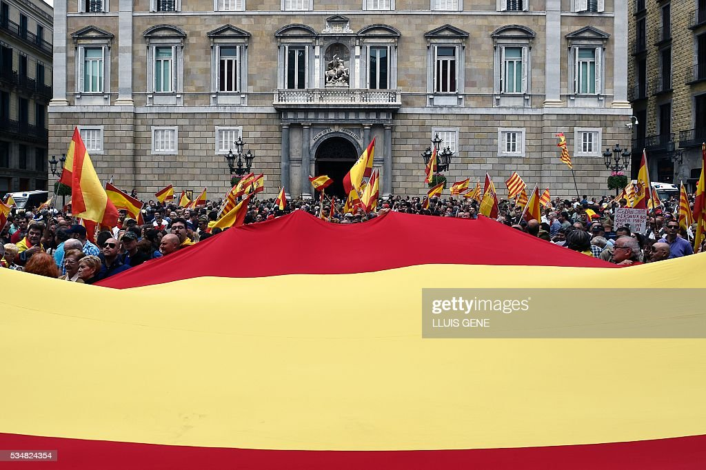 People hold a giant Spanish flag in front of Catalonia's government headquarters during a demonstration in support of the Spanish army organized by 'La Hermandad de Caballeros Legionarios de Barcelona' ( Brotherhood of the Knights Legion of Barcelona) on May 28, 2016 in Barcelona. / AFP / LLUIS