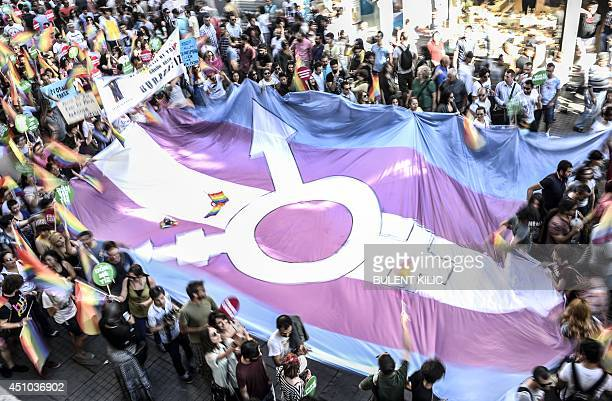 People hold a giant transgender flag during a gay parade on Istiklal Street the main shopping corridor in Istanbul on June 22 during the Trans Pride...