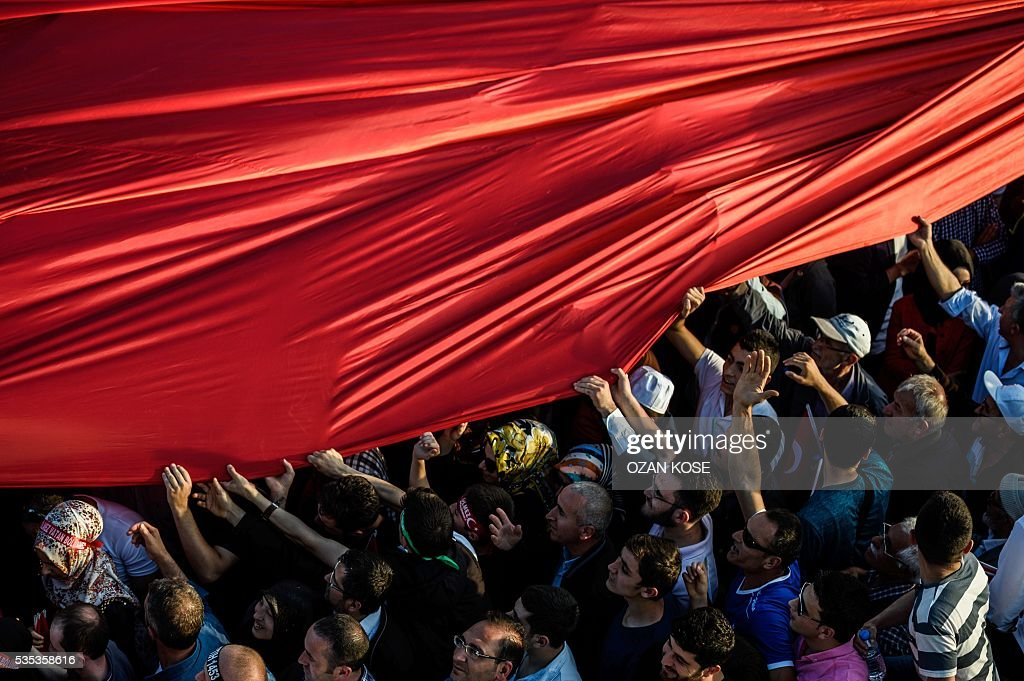 People hold a giant Turkish national flag as Turkish President speaks during a rally to mark the 563rd anniversary of the conquest of Istanbul by Ottoman Turks on May 29, 2016 in Istanbul. / AFP / OZAN