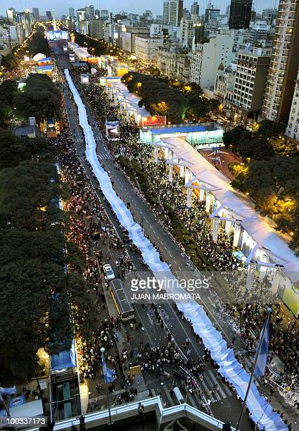 People hold a huge Argentine flag along 9 de Julio avenue in Buenos Aires on May 22 2010 as part of the celebrations for the Bicentenary of the May...