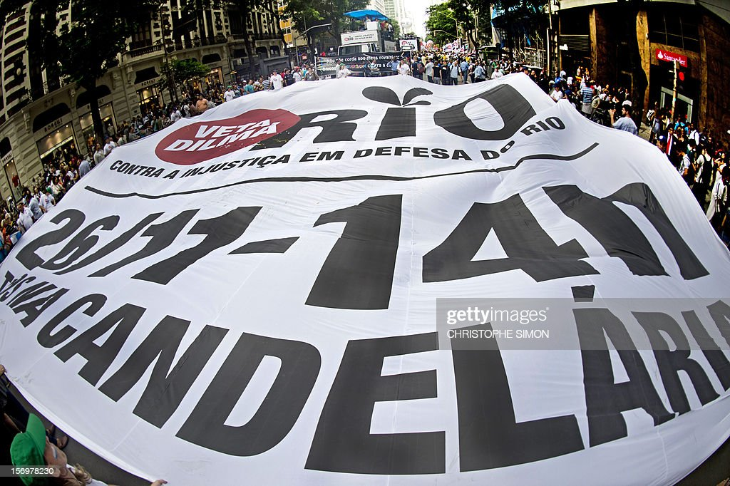 People hold a huge banner during a demonstration demanding Brazilian President Dilma Roussef to veto a bill that would redistribute oil royalties in favor of non-oil producing states, in Rio de Janeiro, Brazil, on November 26, 2012. Both Rio de Janeiro's mayor Eduardo Paes and governor Sergio Cabral warned that the new oil royalties share-out plan will jeopardize the financing of the 2014 World Cup and the 2016 summer Olympics. AFP PHOTO/Christophe Simon