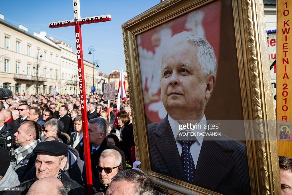 People hold a late Polish President <a gi-track='captionPersonalityLinkClicked' href=/galleries/search?phrase=Lech+Kaczynski&family=editorial&specificpeople=544054 ng-click='$event.stopPropagation()'>Lech Kaczynski</a> portrait as they attend a ceremony attend a ceremony marking the fifth anniversary of the presidential plane crash in Smolensk, in front of the presidential palace in Warsaw, on April 10, 2015.