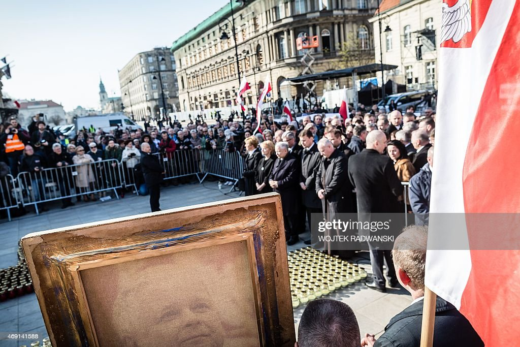 People hold a late Polish President Lech Kaczynski portrait as they attend a ceremony attend a ceremony marking the fifth anniversary of the...