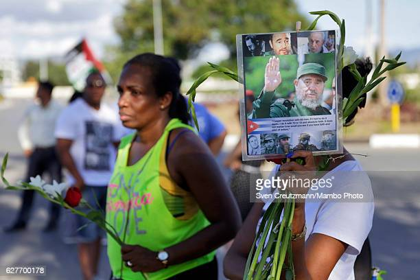People hold a photo of Fidel Castro as they are waiting to visit the grave that holds the ashes of Cubas Revolution leader Fidel Castro at the Santa...