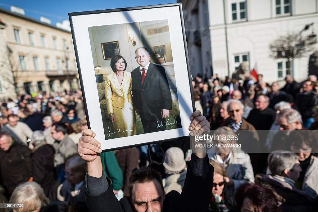 People hold a portrait of late Polish President Lech Kaczynski and his wife Maria as they attend a ceremony marking the fifth anniversary of the...