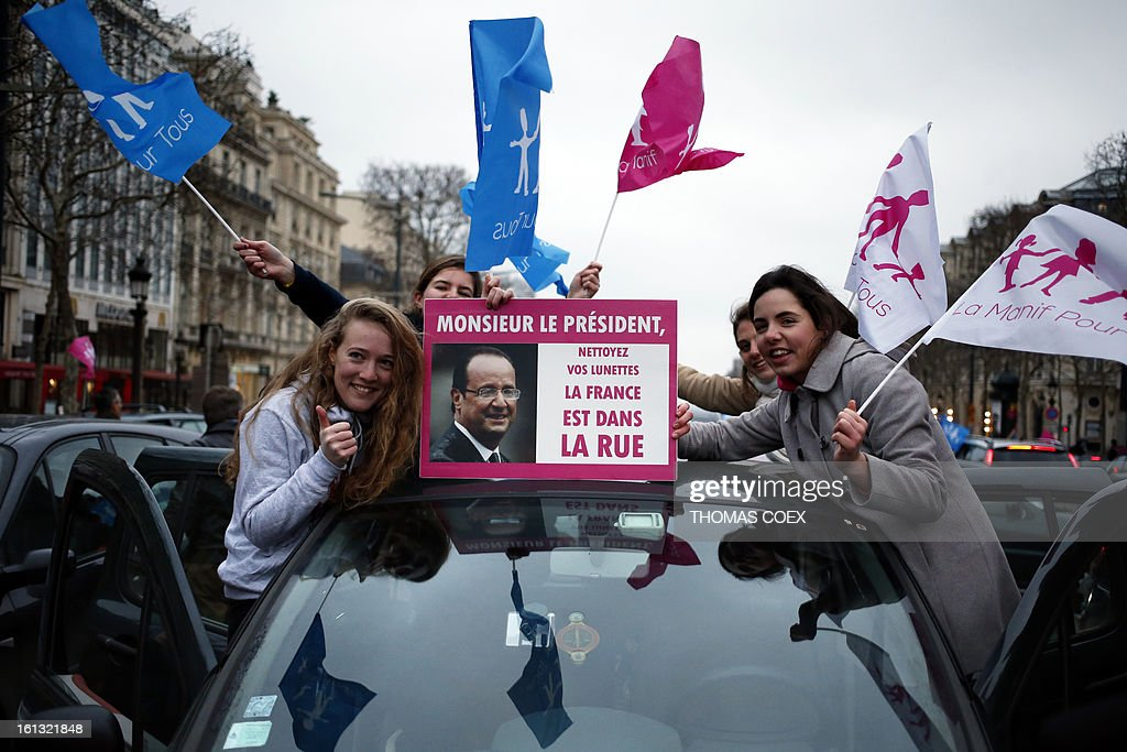 People hold a poster (translation 'Mister President clean your spectacles, France is in the street') in Paris on February 10, 2013 during a demonstration on the Champs Elysees by predominanntly French right wing supporters protesting a proposed law to legalise gay marriage and adoption. France's National Assembly overwhelmingly approved a key piece of legislation that will allow homosexual couples to marry and adopt children, to the delight of gay activists.