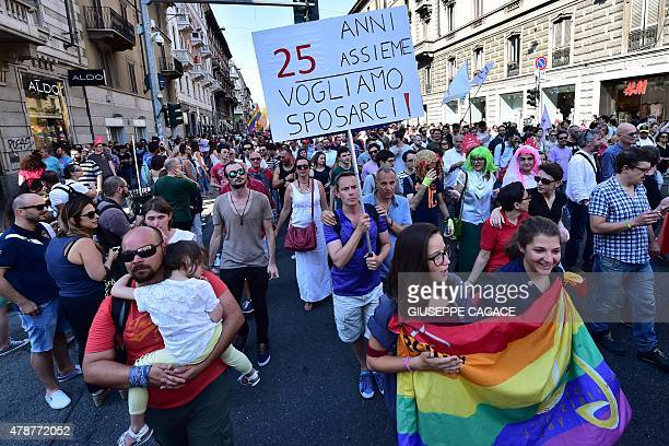 People hold a sign reading '25 years together we want to get married' as they take part in the annual Lesbian Gay Bisexual and Transgender Pride...