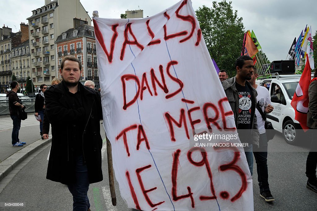 People hold a sign reading a play on words with the name of the French Prime minister during a demonstration against controversial labour reforms on June 28, 2016 in Rennes. Unions have called repeated strikes and marches in opposition to the law, which seeks to bring down France's intractable 10-percent unemployment rate by making it easier to hire and fire workers.