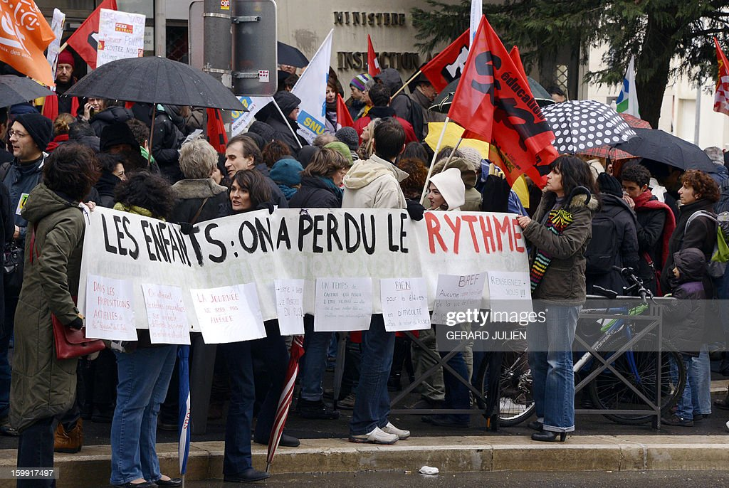 People hold a sign reading 'Children: We have lost the rhythm' as they and other French teachers take part in a nationwide strike and protest action against a proposed reform to increase the class time of primary school students, on January 23, 2013, in Marseille, southern France. The strike and rally was called by French educational trade unions to protest a reform proposition by France's Education Minister, planned for the 2013-2014 schoolyear, which foresees an increase of class time in primary schools to 4.5 days a week and would affect both students and teachers.